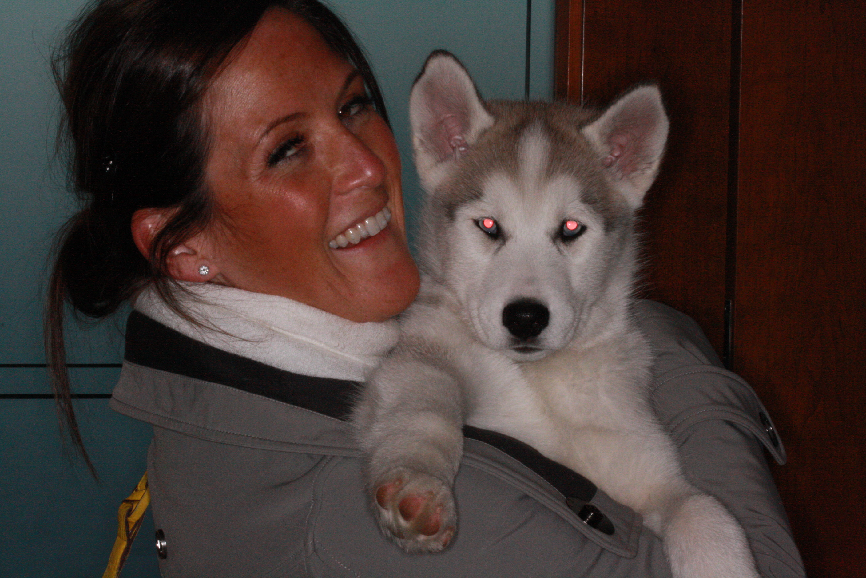 A picture of Kacia smileing holding her husky puppy.
